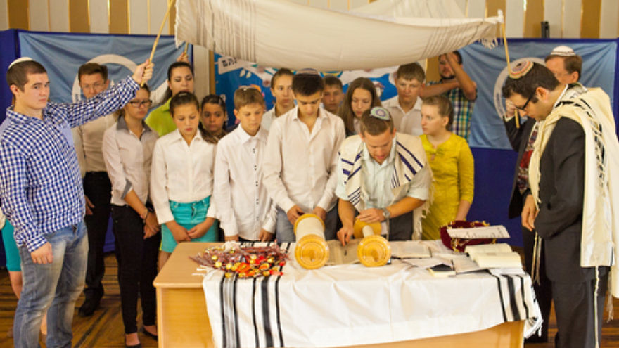 Click photo to download. Caption: Participants in the Bar/Bat Mitzvah Family Camp reading from a Torah scroll in the Siberian city of Novosibirsk in August 2014. Credit: Roman Ibragimov.