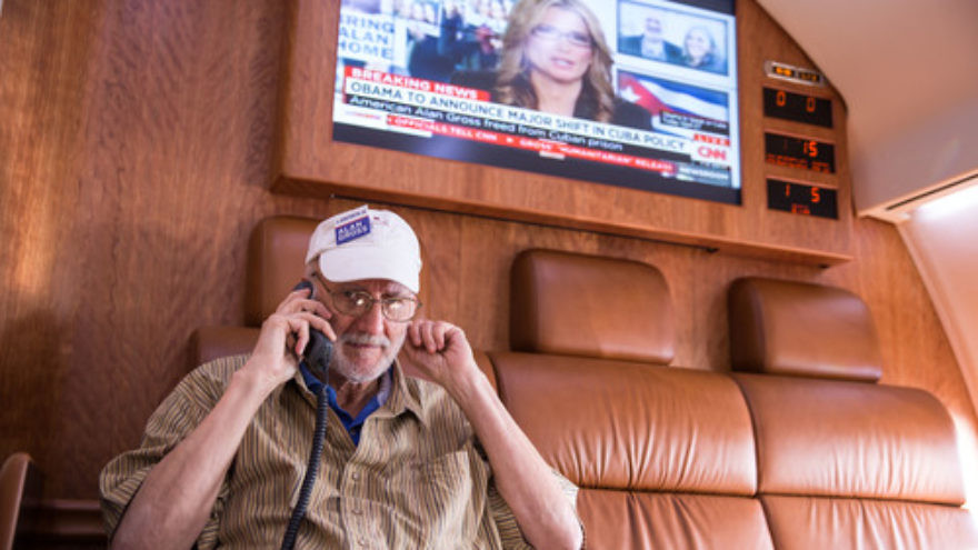 Click photo to download. Caption: After being released from prison in Cuba, Alan Gross speaks on the phone with President Barack Obama during his flight back to the U.S. on Dec. 17. Credit: White House.