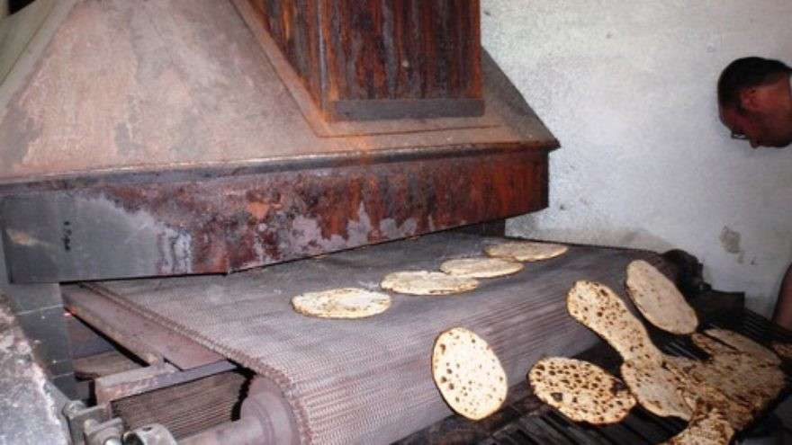 Click photo to download. Caption: Hand-made matzah comes out of the oven. Credit: Ariel Palmon via Wikimedia Commons.
