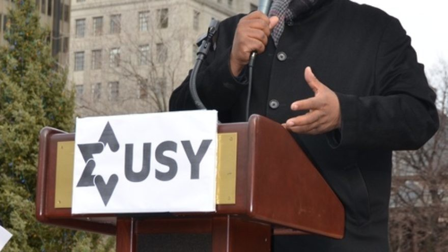 "Click photo to download. Caption: Pastor Corey Brooks of the New Beginnings Church of Chicago speaks at the Dec. 26 ""Praying With Our Feet"" rally against gun violence organized by United Synagogue Youth (USY). Credit: USY."