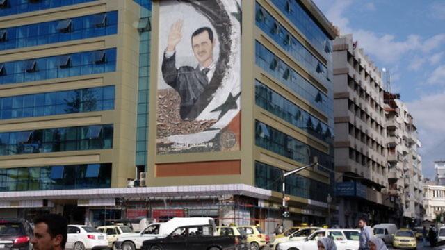 A mural featuring Syrian President Bashar Assad in Latakia, Syria. Credit: Emesik via Wikimedia Commons.