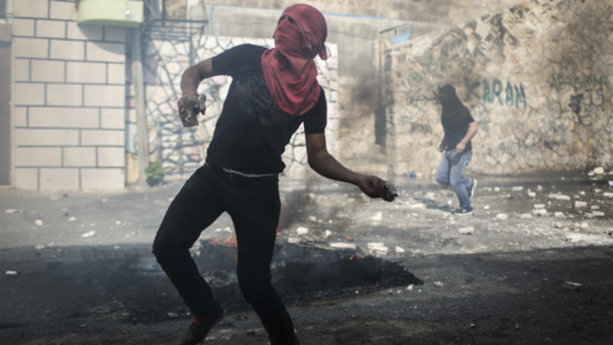 Click photo to download. Caption: On Oct. 30, 2014, a Palestinian rock thrower targets Israeli police in Jerusalem's Abu Tor neighborhood, near the house of the Palestinian man suspected of attempting to assassinate Temple Mount activist Yehudah Glick. Credit: Hadas Parush/Flash90.