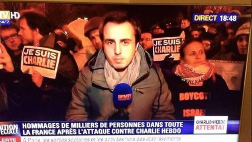 "In this image circulating on social media depicts a news report from the scene of a mourners' rally for the murdered Charlie Hebdo journalists, a woman (pictured on the right) behind the reporter is seen wearing a shirt with the wording ""Boycott Israel,"" seemingly making the statement that Israel is somehow to blame for the attack on the magazine. Credit: Facebook."