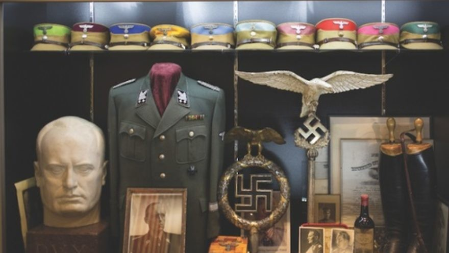 Click photo to download. Caption:  Inside the Solana Beach, Calif., warehouse of Craig Gottlieb. Lining the walls of the warehouse are Nazi military uniforms, iron crosses, swastika flags, and German military propaganda. Credit: Daisy Varley.