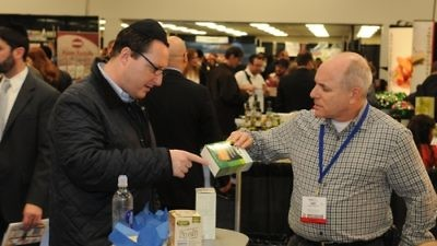 "Click photo to download. Caption: A Kosherfest 2013 vendor speaks with an attendee about Aviva Organic Petit Beurre Biscuits, which Aviva Organic describes as ""delicious healthy cookies made of whole wheat flour, a great healthy treat for children & adult."" On  the table are whole grain spelt crackers from Landau Kosher. Credit: Kosherfest."