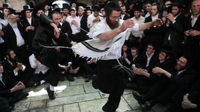 Click photo to download. Caption: Orthodox Jewish men dance as they take part in celebrations of the Jewish holiday of Lag B'Omer at Mount Meron in northern Israel on May 22, 2013. Credit: Yaakov Naumi/Flash90.