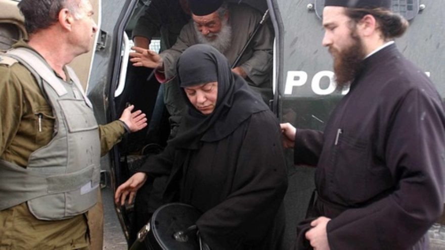 Click photo to download. Caption: An Israeli soldier helps to smuggle out a priest and a nun from the Church of the Nativity in Bethlehem on April 7, 2002. That year, a siege by Palestinian militants on the Church of the Nativity persisted from April 2 to May 10—just days after Easter on the Eastern Orthodox calendar. Credit: Flash90.