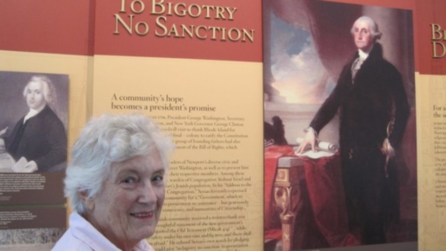 "Rita Eisenberg Slom—a Newport, R.I., native who served as president of the historic Touro Synagogue from 1999-2001—is pictured in the Ambassador John L. Loeb Jr. Visitors Center next to a poster of the famous letter President George Washington addressed ""To the Hebrew Congregation in Newport Rhode Island,"" which is read annually at Touro Synagogue. Credit: Paul Foer."