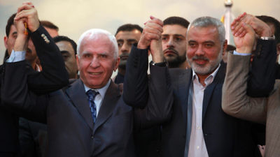 Head of the Hamas government Ismail Haniyeh (right) and senior Fatah official Azzam Al-Ahmed (left) raise their hands together at a news conference that announced a reconciliation agreement between the rival Palestinian factions in Gaza City on April 23, 2014. Credit: Abed Rahim Khatib/Flash90