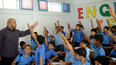 Palestinian boys raise their hands at a school in Gaza supported by the United Nations Relief and Works Agency for Palestine Refugees in the Near East (UNRWA) in September 2011. Credit: U.N. Photo/Shareef Sarhan.