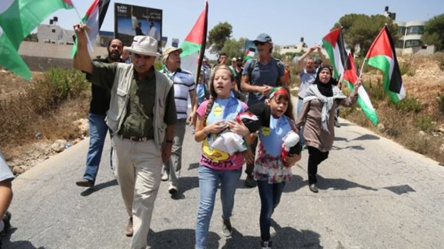 "Palestinian demonstrators in Nabi Saleh hold Palestinian Authority flags during a protest against Jewish settlement expansion in August 2015. Nearly every Friday for the past seven-and-a-half years, ""Palestinian supermom"" Manal Tamimi and her colleagues in Nabi Saleh have marched to the nearby Jewish community of Halamish to demand its expulsion. Credit: Flash90."