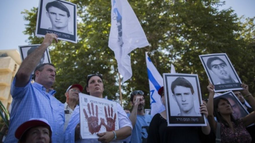 Click photo to download. Caption: On July 28, relatives of Israelis killed in terror attacks hold signs as they demonstrate outside of the Prime Minister's Office ahead of the Israeli cabinet vote on the proposal to free 104 terrorist prisoners for the restarting of Israel-Palestinian conflict talks. The prisoner release proposal passed in a 13-7 vote. Credit: Yonatan Sindel/Flash90.