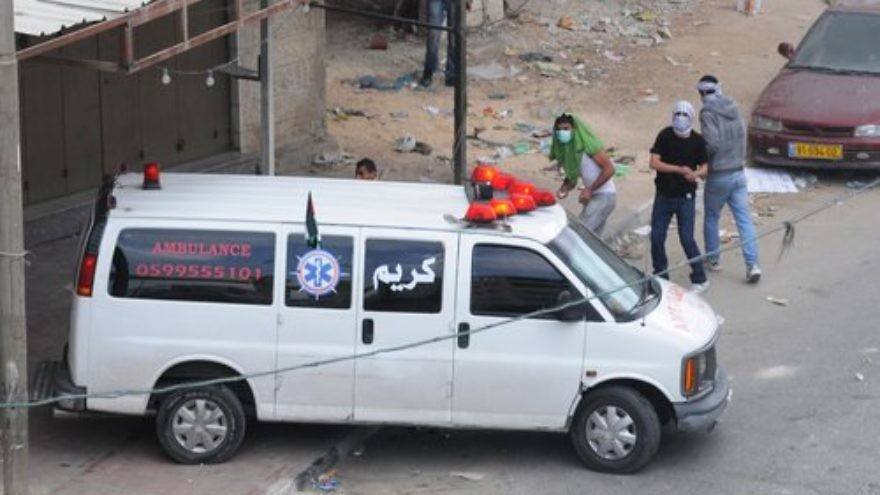 Palestinians throw rocks from behind an ambulance during a riot in Qalandiya. Credit: IDF.