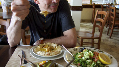"Film director Roger Sherman samples Israeli cuisine. Credit: ""In Search of Israeli Cuisine"" press photo."