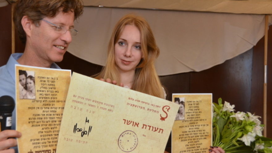 "Boaz Bau-Simon, the grandson of Joseph and Rebecca Bau, with his fiancé Or (Irena) Gatina in February 2014. The couple announced its engagement at the ceremony commemorating the 70th wedding anniversary of Bau-Simon's grandparents. Bau-Simon and Gatina are pictured holding a ""teudat osher"" (""certificate of happiness"") originally created by Joseph Bau as well as a letter relating the story of the lifelong romance of Joseph and Rebecca Bau. Credit: Maxine Dovere."