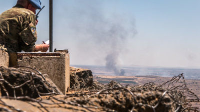 A U.N. observer is stationed at a lookout point as smoke rises in a Syrian village near the Israel border in the Golan Heights during fighting in the Syrian civil war, June 25, 2017. Credit: Basel Awidat/Flash90.