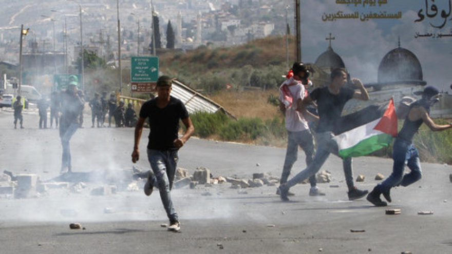 "Palestinians hurl stones at Israeli security forces during a demonstration at the Hawara checkpoint, near Nablus, amid Muslim riots over Jerusalem's Temple Mount holy site July 21, 2017. Israel Hayom last week quoted a Palestinian Authority security official as claiming that Iran's regime invested ""millions of shekels"" to inflame the tensions surrounding the Temple Mount. Credit: Nasser Ishtayeh/Flash90"