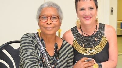 Click photo to download. Caption: Author Alice Walker and playwright Eve Ensler clasp hands at the 92nd Street Y in New York City on the night they appeared together in dialogue, May 30. Credit: Maxine Dovere.