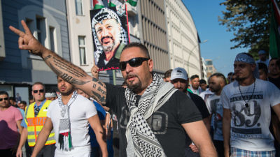 In July 2014 in Berlin, demonstrators carry a picture of late Palestinian leader Yasser Arafat and protest against the Israeli military's Operation Protective Edge in Gaza. Credit: Boris Niehaus via Wikimedia Commons.