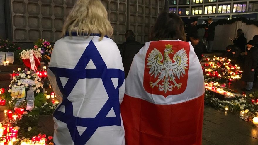 On Dec. 19, Antje Böttinger (left), wrapped in an Israeli flag, and a woman wearing a Polish flag visit a memorial to victims of the December 2016 Berlin Christmas market terror attack. Credit: Orit Arfa.
