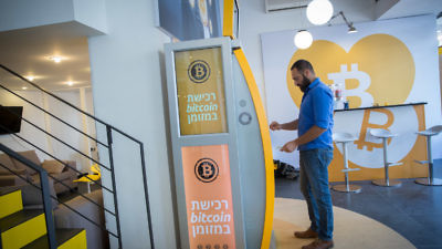 On Nov. 5, a man uses a bitcoin ATM machine at the Bitcoin Change center on Dizengoff Street in Tel Aviv. The center houses the ATM as well as a museum on the history of the cryptocurrency. Credit: Miriam Alster/Flash90.