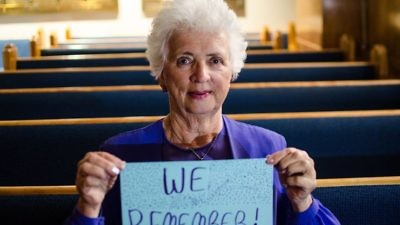 "A woman holds a ""We Remember"" sign as part of the the World Jewish Congress's social media campaign. Credit: Facebook."