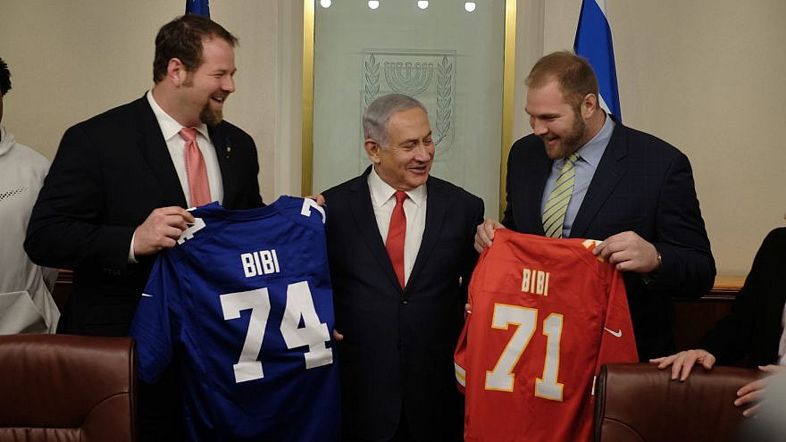 "Jewish NFL football players and brothers Geoff (left) and Mitchell Schwartz present Israeli Prime Minister Benjamin Netanyahu with football jerseys that have his nickname, ""Bibi,"" on them in his Jerusalem office on Feb. 19, 2018. (Judah Ari Gross/Times of Israel)"