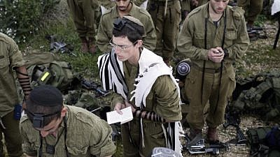 Soldiers in the Neztah Yehuda Battalion complete the final stages of a 40-kilometer journey during the night on Feb. 16, 2010. Other military practices are being debated by a group of rabbis in Israel. Photo by Abir Sultan/Flash90
