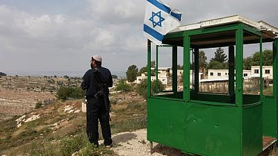 An Israeli security guard at his post, at Bat Ain settlement, Gush Etzion. Credit: Nati Shohat/Flash90.