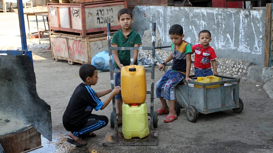 File photo: Palestinians fill plastic bottles and jar cans with drinking water from a public tap in the southern Gaza Strip refugee camp of Rafah, on July 26, 2015.  Photo by Abed Rahim Khatib / Flash 90