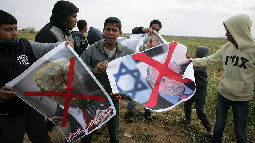Palestinians demonstrate with posters marring the images of Israeli Prime Minister Benjamin Netanyahu and U.S. President Donald Trump during a protest near Khan Yunis in the southern Gaza Strip on March 30, 2018. Credit: Abed Rahim Khatib/Flash90