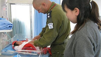 An Israeli army doctor treats a baby following the 2011 earthquake in Japan. Credit: Flickr.
