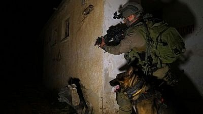 A member of the Givati infantry brigade trains in a simulated urban warfare scenario with his canine companion. Credit: IDF Spokesperson Unit.