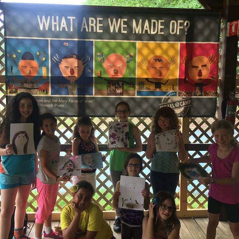 Campers show off their Hanoch Piven-inspired portraits in front of their Israel @ Camp banner. Credit: iCenter for Israel Education.