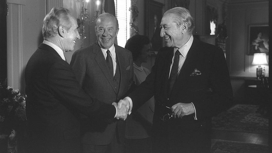 Israeli Prime Minister Shimon Peres (left) shakes hands with U.S. Jewish industrialist Max Fisher at reception given by U.S. Secretary of State George Shultz (center). Photo by Chanania Herman/GPO.