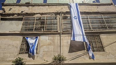 Israeli flags hang on the new Beit Rachel and Beit Leah buildings in Hebron. Photo by Yishai Fleisher