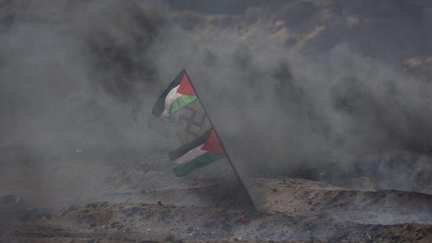 Palestinians display a flag with a swastika in the middle during Gaza border protests in April 2018. Credit: IDF via Twitter.