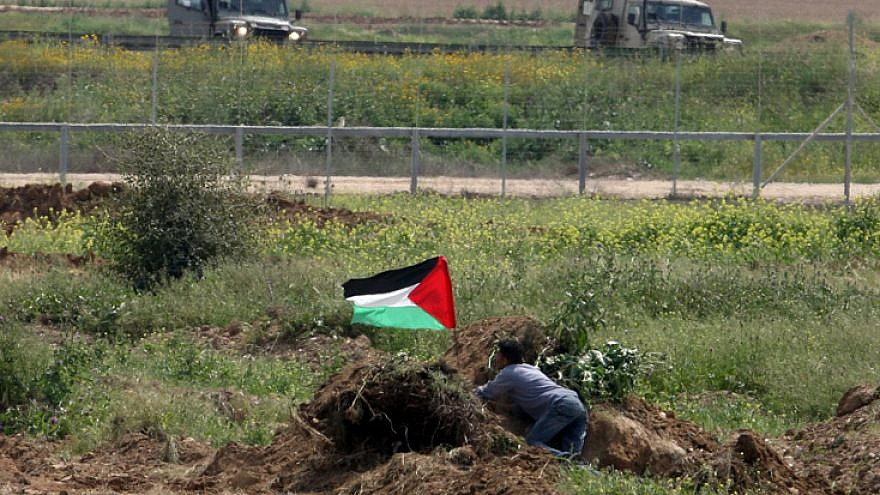 A Palestinian man waves the Palestinian flag near Israeli soldiers by the border fence near Gaza City in March 2010. Photo by Wissam Nassar/Flash90.