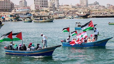 """Palestinians hold flags as they ride a boat during a rally marking the fifth anniversary of the """"Mavi Marmara"""" Gaza flotilla, at the seaport of Gaza City on May 31, 2015. Photo by Aaed Tayeh/Flash90."""