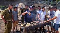 """Israeli soldiers enjoy a barbecue prepared for them in honor of Israel's Independence Day in 2016 at the """"soldiers corner,"""" a place to rest and eat at the Gush Etzion junction. Credit: Gershon Elinson/Flash90."""