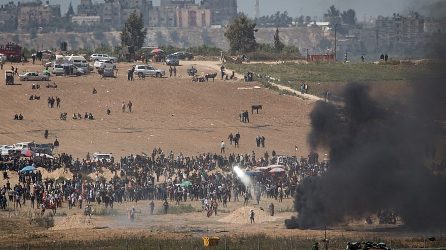 Palestinian protesters attempt to blind IDF snipers with mirrors as they demonstrate and burn tires near the border with Israel in the Gaza Strip as seen from the Israeli side of the border