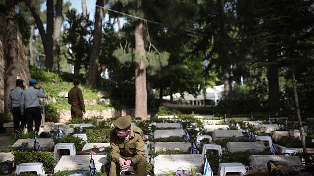 An Israeli soldier sits next to grave of fallen soldier at the Mount Herzl military cemetery in Jerusalem during Israeli Memorial Day, which commemorates the deaths of Israeli soldiers killed in wars since 1860, as well as Israeli victims of terror. April 18, 2018. Photo by Miriam Alster/Flash90