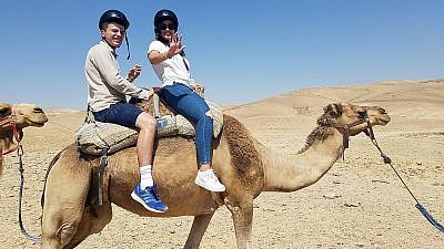 Julian Reiss, 21, left, riding a camel in the Israeli desert with a travel guide. (Courtesy of the Friendship Circle)