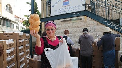 Volunteer Rita Lewy displays a loaf of challah at the Terror Victims Support Center. Credit: Courtesy.