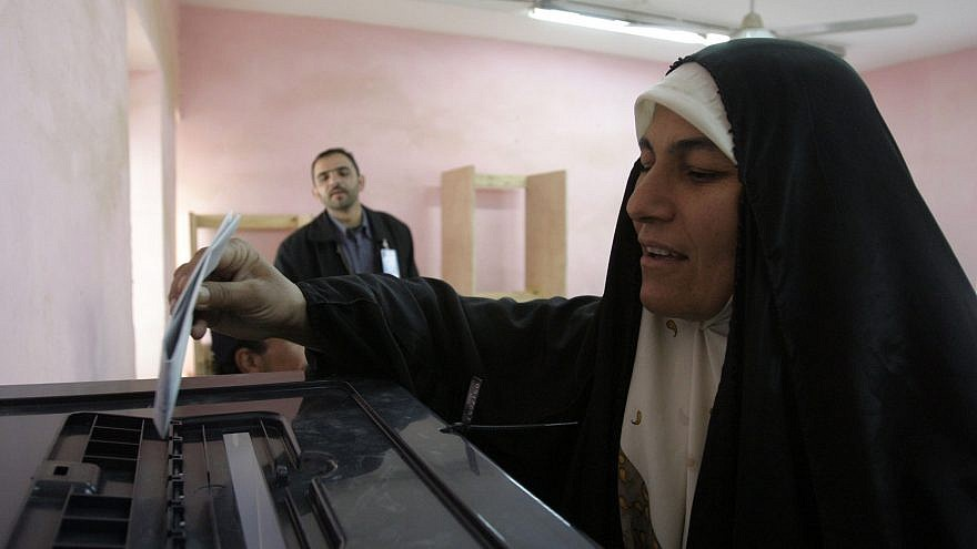 An Iraqi woman prepares to cast her voting ballot after filling it out at a polling site in Rawah, Iraq, during the country's first parliamentary election in December 2005. U.S. Marine Corps Photo by Lance Cpl. Shane S. Keller/Wikimedia Commons