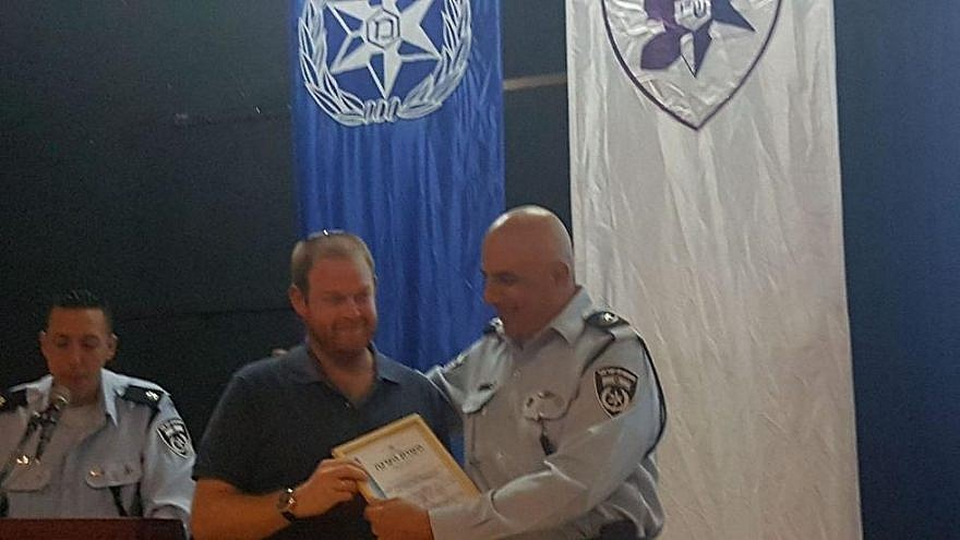 Ofek Kaufman earns an award for his quick action in helping a man who was fleeing from an attacker. Source: Israel Police.