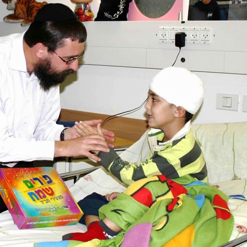 "Rabbi Menachem Kutner, director of the Chabad Terror Victims Project, brings a gift to Ural Yelizarov, who was wounded in the head by a Grad rocket in Beersheva during ""Operation Cast Lead."" Credit: CTVP"