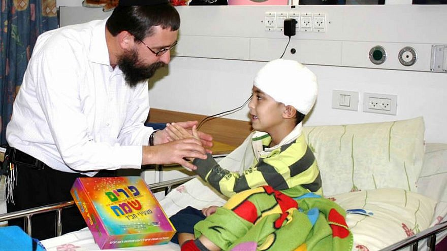 "Rabbi Menachem Kutner, director of the Chabad Terror Victims Project, brings a gift to Ural Yelizarov, who was wounded in the head by a Grad rocket in Beersheva during ""Operation Cast Lead"" in 2014. Credit: CTVP."