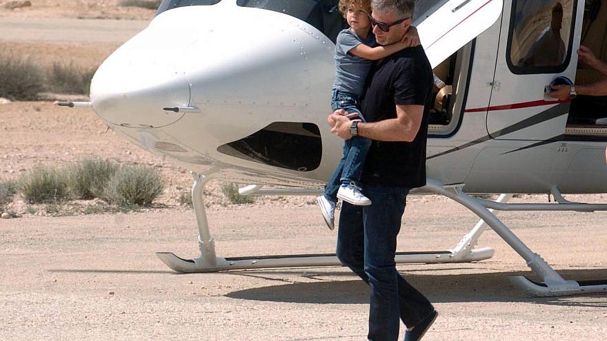 Carrying one of his children, Russian Jewish billionaire Roman Abramovich arrives at the Beresheet Hotel in Mitzpe Ramon in southern Israel on April 14, 2014, Photo by Flash90.