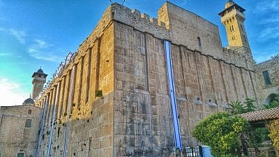 Israel flags decorate the 2,000-year-old Tomb of Machpelah complex in Hebron in anticipation of Yom Ha'atzmaut. The same Herodian masonry is used for the Western Wall in Jerusalem. Photo by Yishai Fleisher.